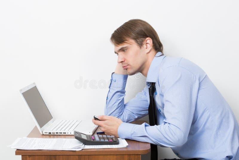 O homem de negócios considerável está trabalhando com portátil dentro fotos de stock