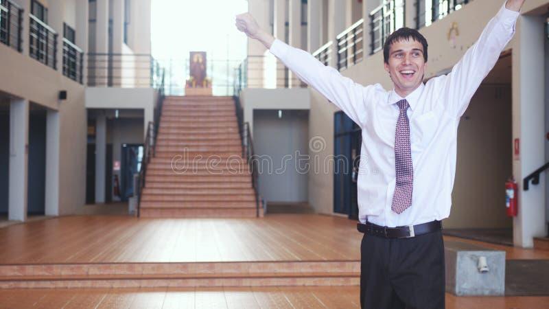 O homem de negócios considerável feliz está com levantar as mãos da alegria no escritório moderno Conceito do negócio, economia,  imagens de stock