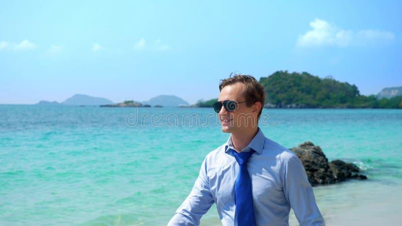 O homem de negócios considerável nos óculos de sol andou ao longo de uma praia tropical, decolando seu laço imagens de stock