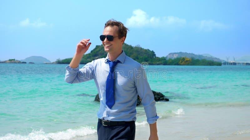 O homem de negócios considerável nos óculos de sol andou ao longo de uma praia tropical, decolando seu laço foto de stock royalty free