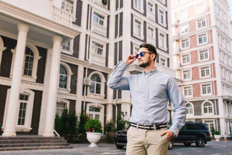 O homem de negócios considerável nos óculos de sol está andando em torno do quarto britânico Guarda a mão no bolso, olhando seria imagem de stock