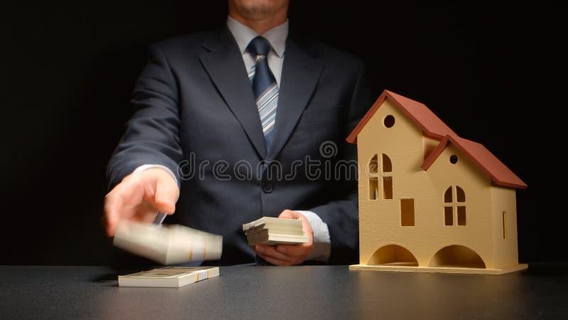 O homem de negócios conta um dinheiro e perto de um modelo da casa em uma tabela imagens de stock royalty free