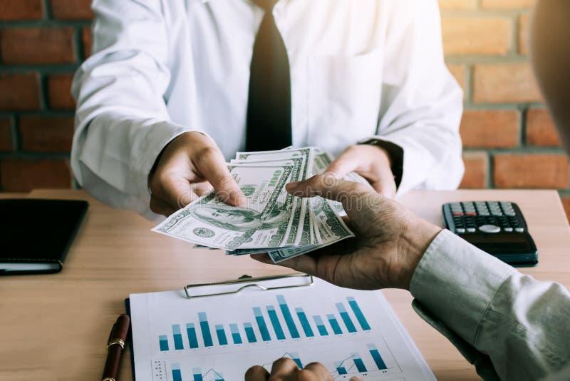 O homem de negócios dá notas de dólar ao sócio fotos de stock
