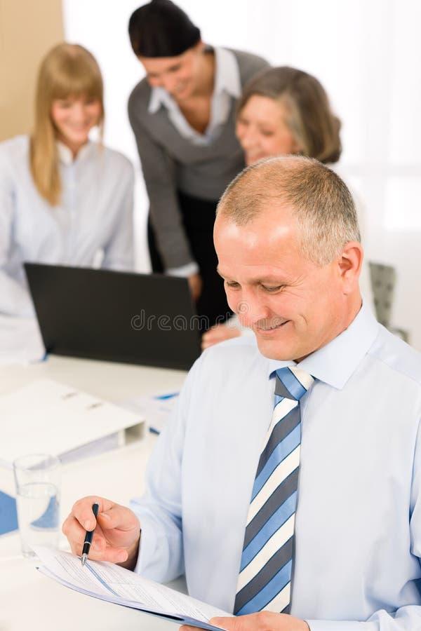 O homem de negócios de sorriso leu o relatório durante a reunião fotos de stock
