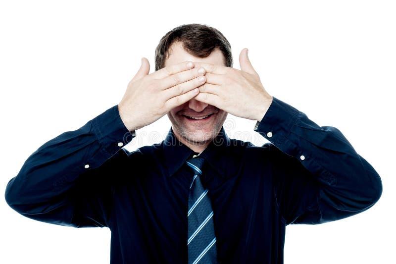 O homem de negócios de sorriso pôs suas mãos sobre os olhos imagem de stock