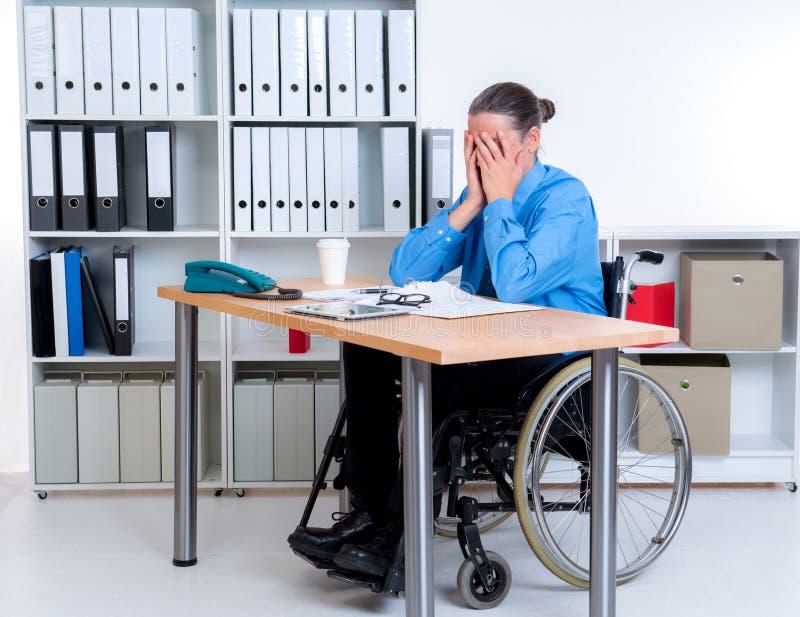 O homem de negócios deficiente na cadeira de rodas é deprimido fotos de stock