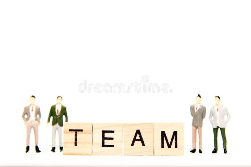 O homem de negócios diminuto do grupo que está com palavras de conceitos da equipe do negócio recolheu nas palavras cruzadas fotos de stock