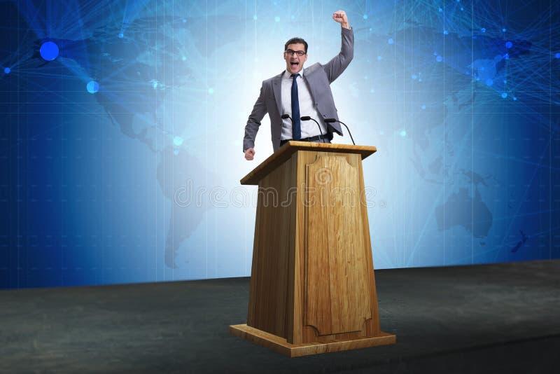 O homem de negócios do homem que faz o discurso na tribuna no conceito do negócio foto de stock