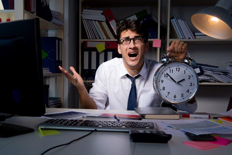 O homem de negócios do homem que trabalha horas atrasadas no escritório imagem de stock