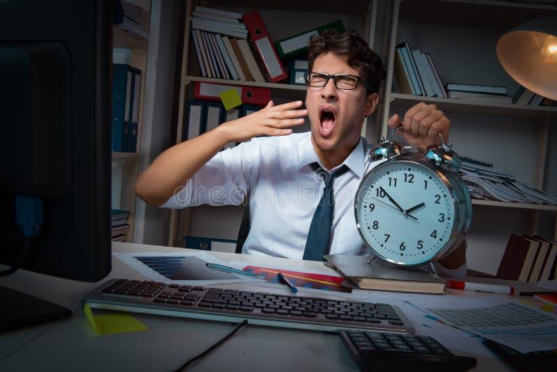O homem de negócios do homem que trabalha horas atrasadas no escritório imagens de stock royalty free