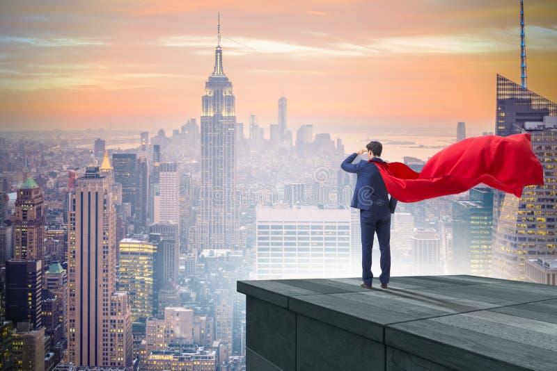 O homem de negócios do super-herói sobre a construção pronta para o desafio fotos de stock royalty free