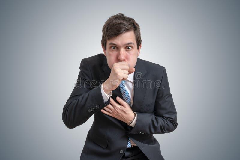 O homem de negócios doente novo está tossindo imagens de stock royalty free