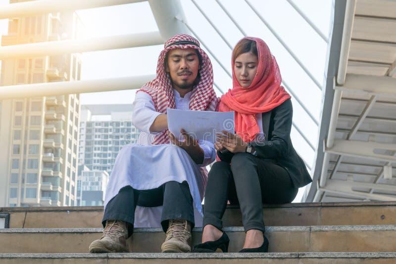 O homem de negócios e a mulher de negócios árabes verificam o gráfico no papel fotos de stock