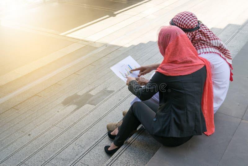 O homem de negócios e a mulher de negócios árabes verificam o gráfico no papel, finança fotos de stock royalty free