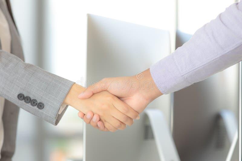 O homem de negócios e a mulher de negócios agitam as mãos para o trabalho do trabalho junto foto de stock