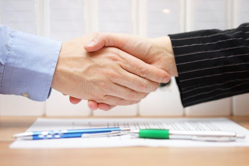 O homem de negócios e a mulher de negócios são aperto de mão assinado sobre contra imagem de stock