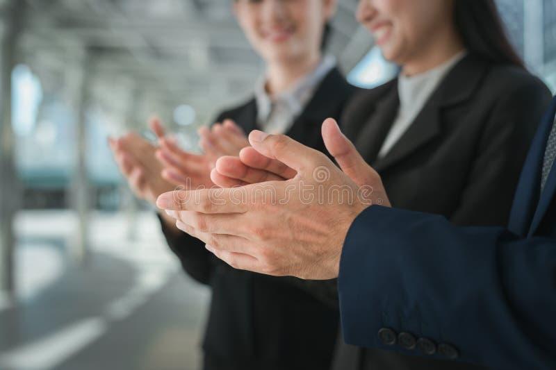 O homem de negócios e a mulher de negócio aplaudem suas mãos para felicitar a assinatura de um acordo ou de um contrato entre sua foto de stock