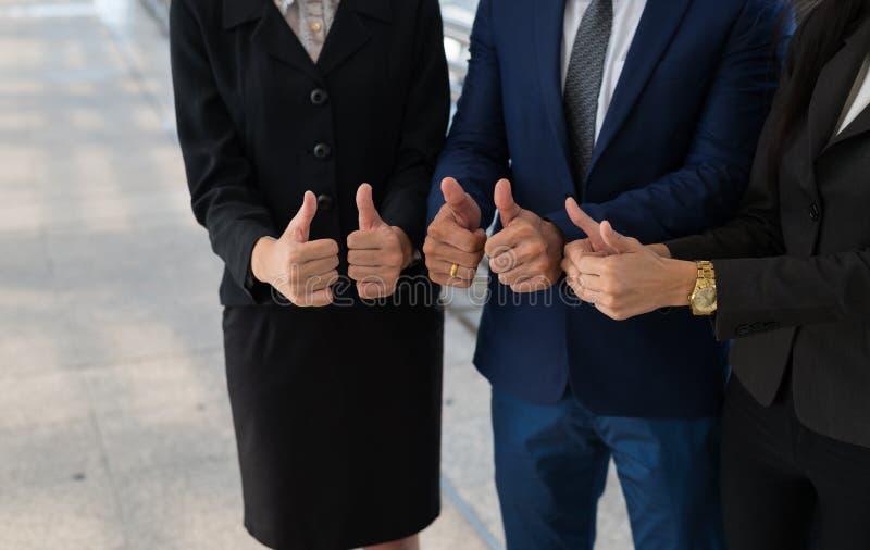 o homem de negócios e a mulher de negócios sorriem e mostram o polegar acima da mão dois, fotografia de stock