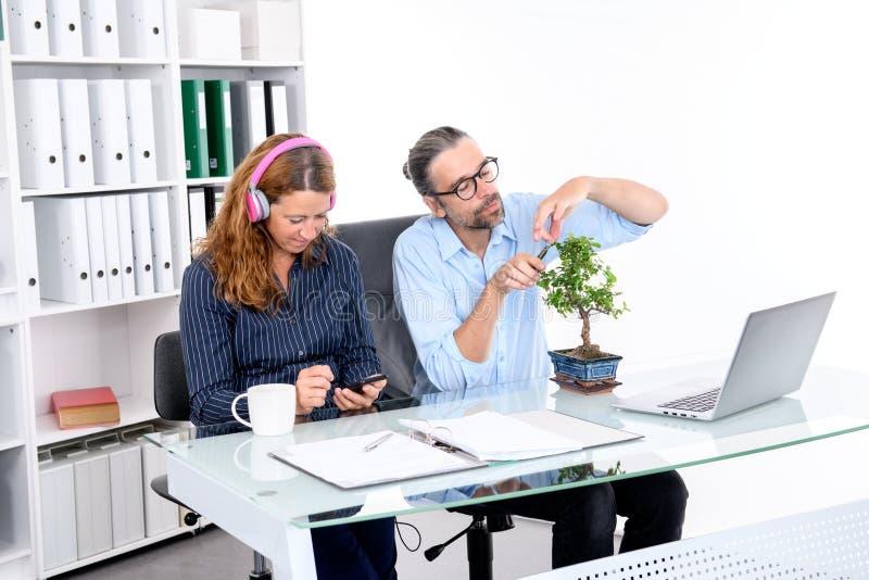 O homem de negócios e a mulher de negócios têm uma ruptura junto no offic imagem de stock
