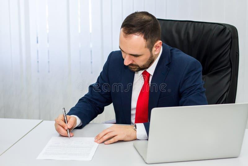 O homem de negócios em um terno azul com um laço vermelho assina um contrato de c foto de stock royalty free