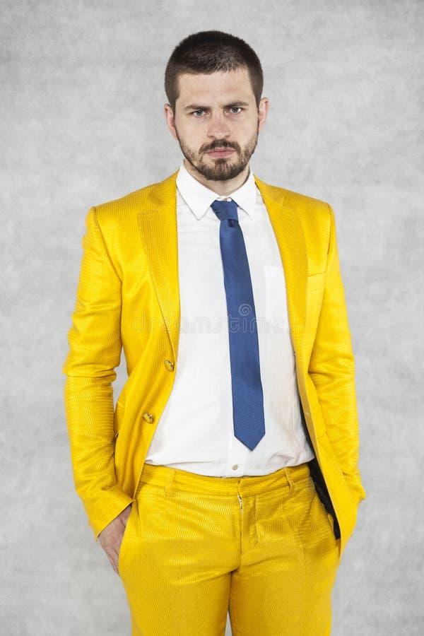 O homem de negócios em um terno do ouro está muito seguro imagens de stock royalty free