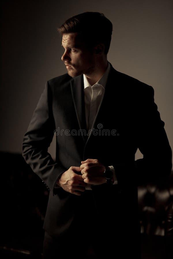 O homem de negócios em um terno e em uma camisa é ereto e ponderando t fotografia de stock royalty free