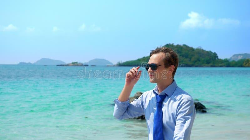 O homem de negócios em uma camisa e em um laço, nos óculos de sol vai em um Sandy Beach branco conceito freelancing, férias fotos de stock