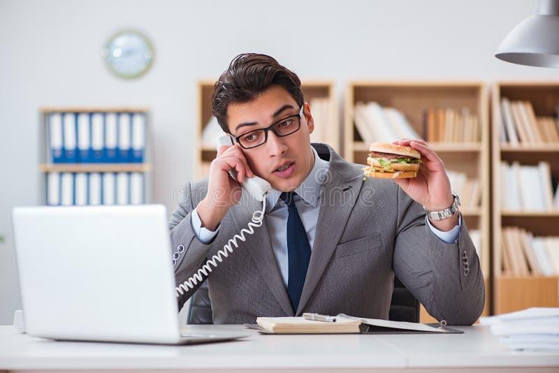 O homem de negócios engraçado com fome que come o sanduíche da comida lixo imagem de stock royalty free