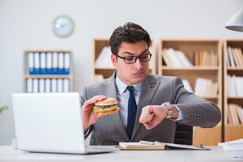 O homem de negócios engraçado com fome que come o sanduíche da comida lixo fotografia de stock royalty free