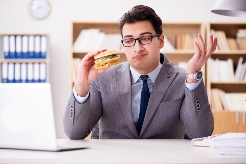 O homem de negócios engraçado com fome que come o sanduíche da comida lixo imagem de stock