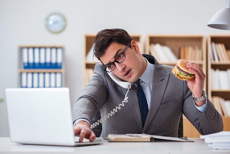 O homem de negócios engraçado com fome que come o sanduíche da comida lixo imagens de stock