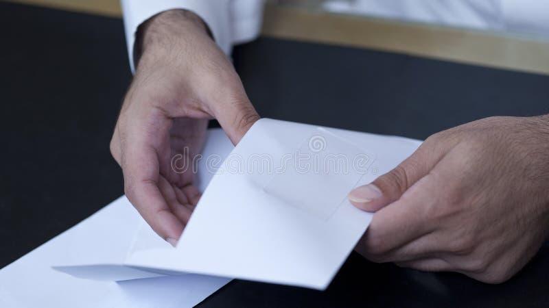 O homem de negócios entrega a abertura de um envelope foto de stock royalty free
