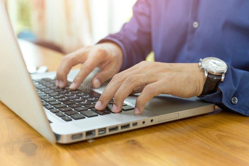 O homem de negócios entrega a datilografia em um laptop na mesa de madeira no escritório imagens de stock royalty free