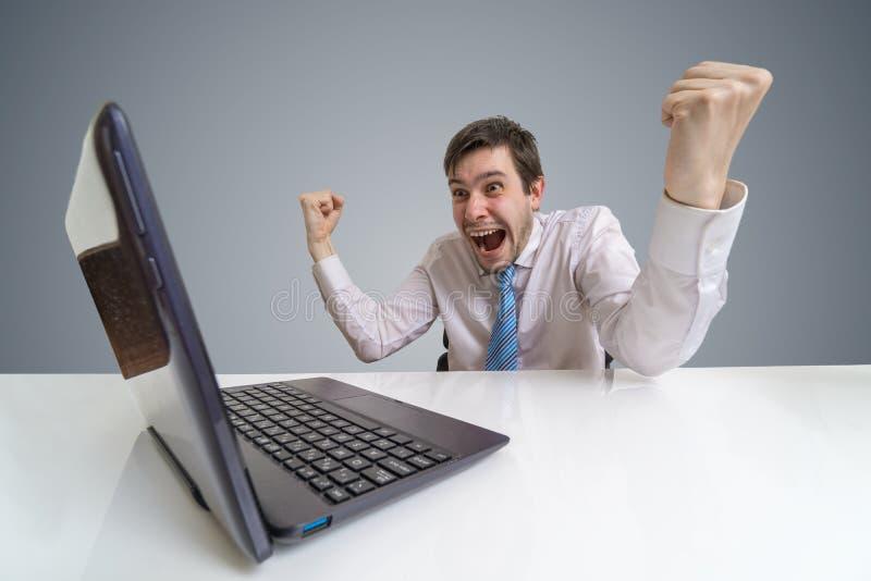 O homem de negócios entusiasmado e feliz novo é um vencedor imagens de stock royalty free