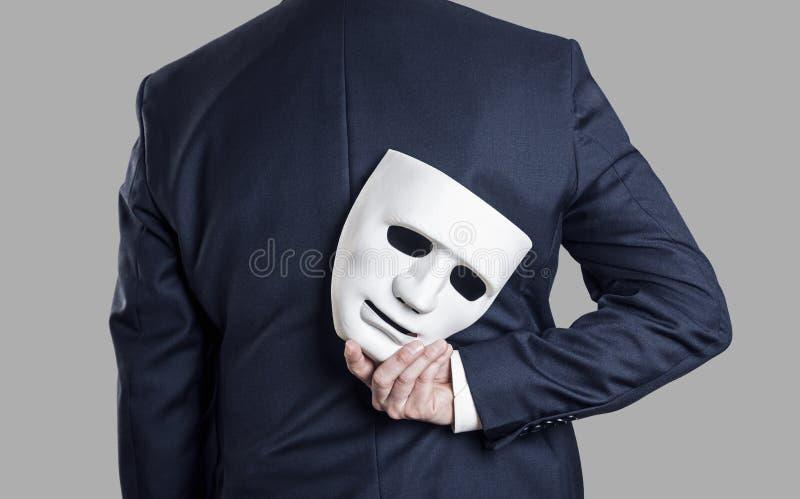 O homem de negócios esconde a máscara à disposição atrás do seu para trás fotografia de stock royalty free