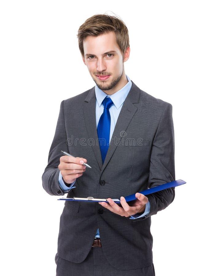 O homem de negócios escreve na prancheta fotografia de stock royalty free