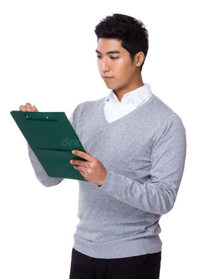 O homem de negócios escreve na prancheta imagens de stock