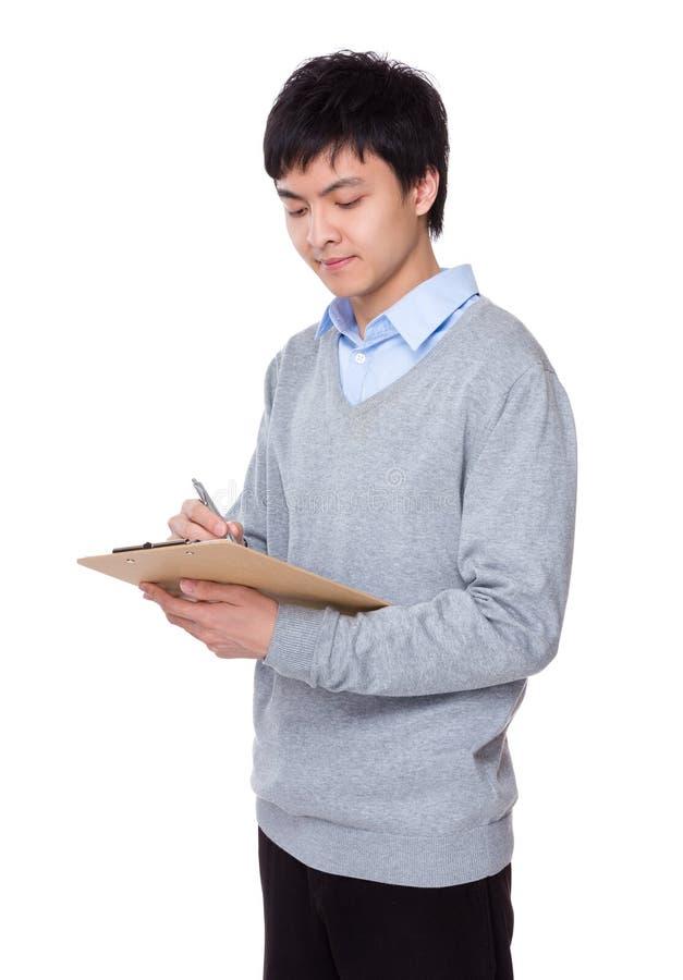 O homem de negócios escreve na prancheta foto de stock royalty free