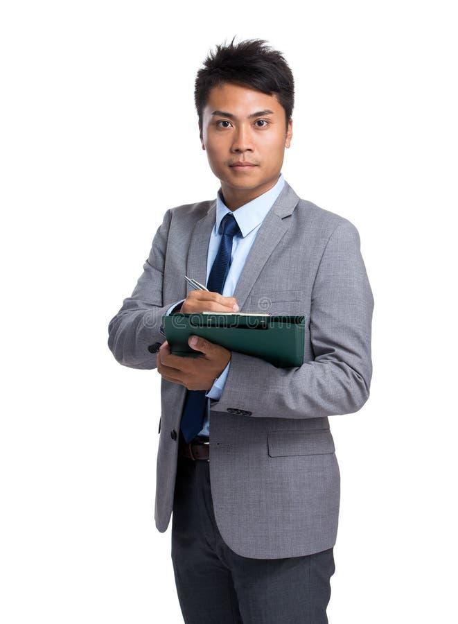 O homem de negócios escreve na prancheta imagem de stock