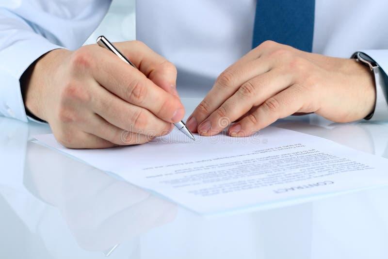 O homem de negócios está assinando um contrato, detalhes do contrato do negócio fotografia de stock