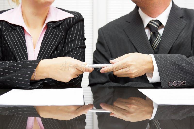 O homem de negócios está dando a pena ao sócio comercial para assinar o contrato fotos de stock royalty free