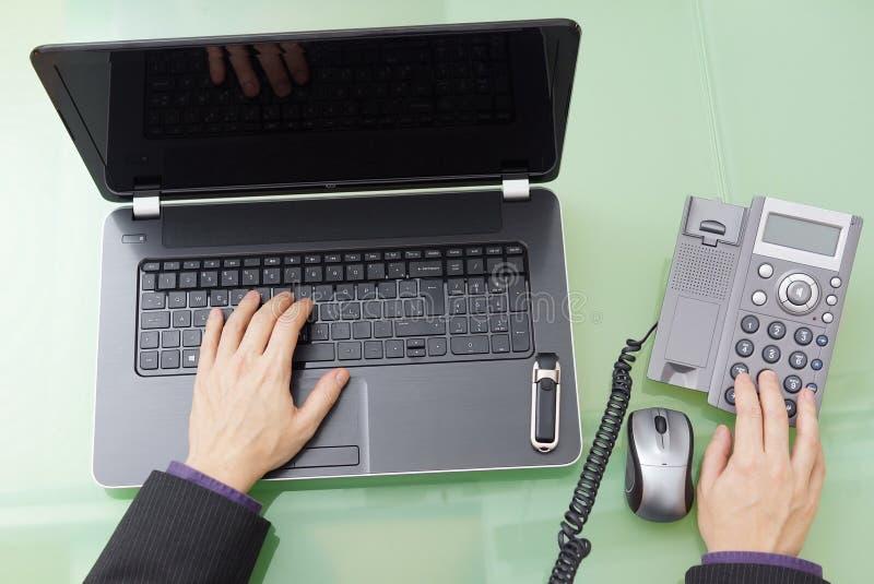 O homem de negócios está discando para o apoio e está trabalhando no portátil fotografia de stock