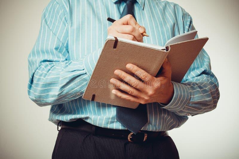 O homem de negócios está escrevendo no caderno, meio corpo foto de stock royalty free