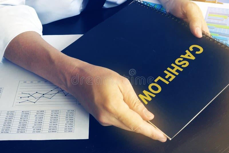O homem de negócios está guardando o livro com cashflow do nome imagens de stock royalty free