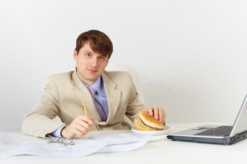 O homem de negócios está indo comer o sanduíche delicioso imagens de stock