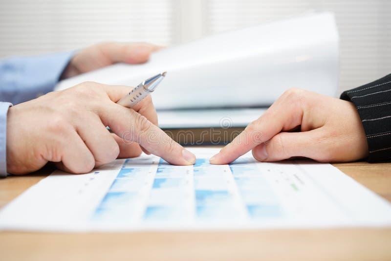 O homem de negócios está lendo o relatório e está discutindo dados comerciais com fotografia de stock