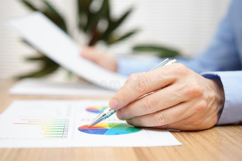 O homem de negócios está lendo o relatório e está verificando dados no gráfico fotos de stock