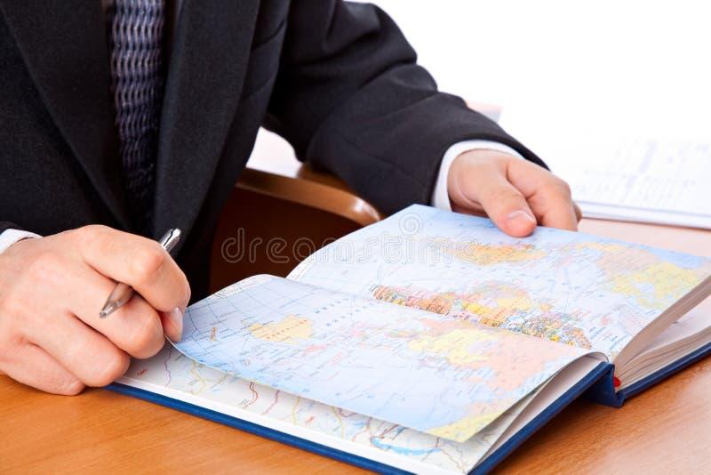 O homem de negócios está olhando no mapa no organizador imagem de stock