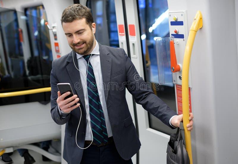 O homem de negócios está olhando seu telefone celular fotografia de stock royalty free