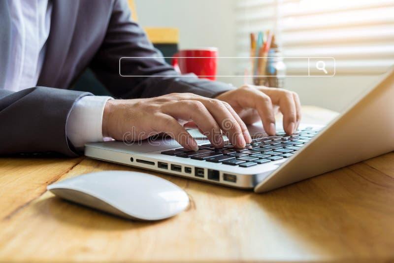 O homem de negócios está sentando a pesquisa pela informação fotografia de stock royalty free